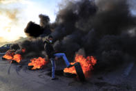 A protester kicks a burning tire to block a highway that links to the Beirut's international airport, during a protest against against the economic and financial crisis, in Beirut, Lebanon, Tuesday, March 2, 2021. The Lebanese pound has hit a record low against the dollar on the black market as the country's political crisis deepens and foreign currency reserves dwindle further. (AP Photo/Hussein Malla)
