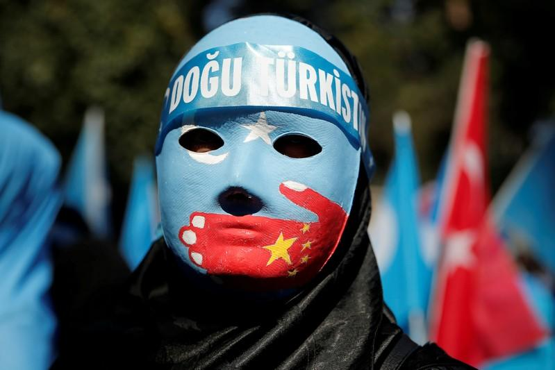 FILE PHOTO: An ethnic Uighur demonstrator wears a mask as she attends a protest against China in front of the Chinese Consulate in Istanbul