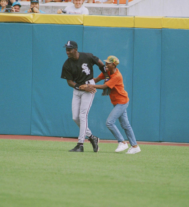 A fan holds on to Michael Jordan of the Chicago White Sox, Sunday, March 20, 1994 in Miami as he played right field against the Florida Marlins at Joe Robbie Stadium. The fan was escorted out of the stadium. (AP Photo/Wayne Fleisher)