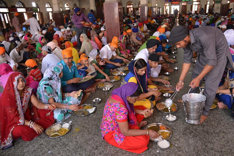 Sikh devotees eat a communal vegetarian meal, known as langar, in a hall at the Golden temple in Amritsar in 2015. (Photo: NARINDER NANU via Getty Images)