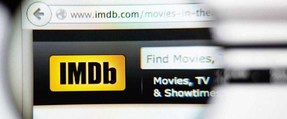 LISBON, PORTUGAL - June 6, 2015. Photo of IMDB homepage on a monitor screen through a magnifying glass.