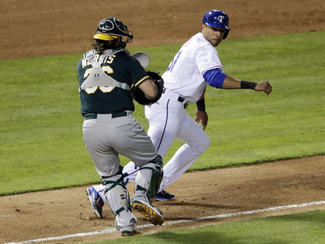 Oakland Athletics' Derek Norris chases down and tags out Texas Rangers' Alex Rios who was trying to score from third on a fielders choice by Leonys Martin in the fourth inning of a baseball game, Tuesday, April 29, 2014, in Arlington, Texas. (AP Photo/Tony Gutierrez)