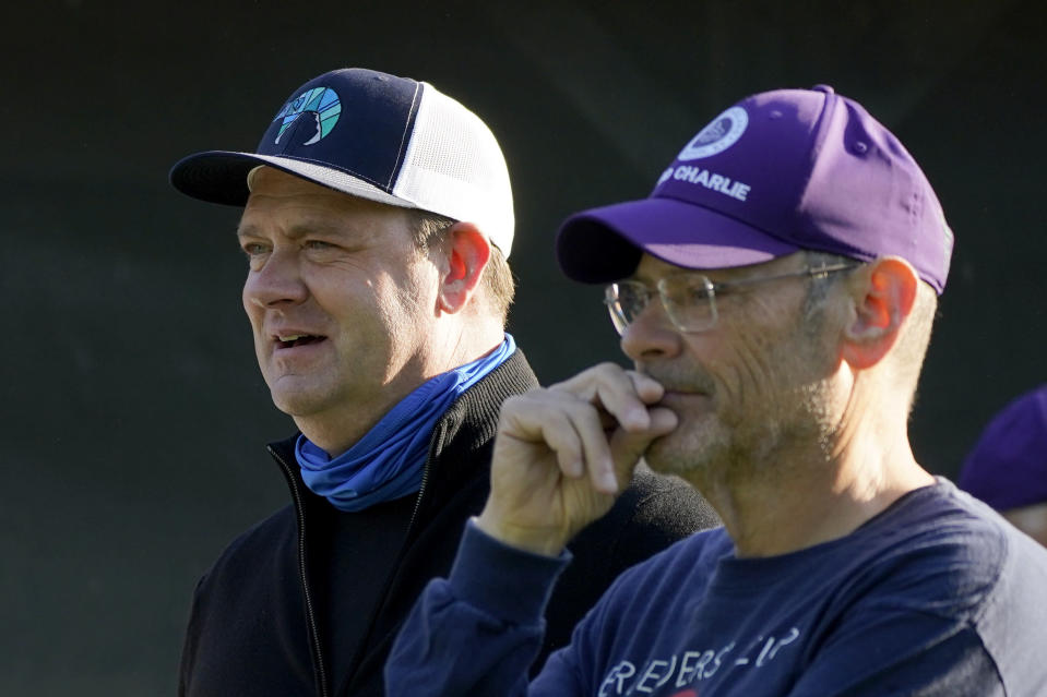 Trainer Doug O'Neill, left, and Bill Strauss, co-owner of Kentucky Derby hopeful Hot Rod Charlie, talk outside their barn after a workout at Churchill Downs Tuesday, April 27, 2021, in Louisville, Ky. The 147th running of the Kentucky Derby is scheduled for Saturday, May 1. (AP Photo/Charlie Riedel)