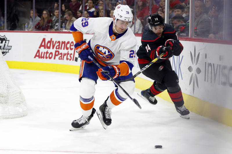 New York Islanders' Brock Nelson (29) moves the puck away from a charging Carolina Hurricanes' Justin Williams (14) during the second period of an NHL hockey game in Raleigh, N.C., Sunday, Jan. 19, 2020. (AP Photo/Karl B DeBlaker)