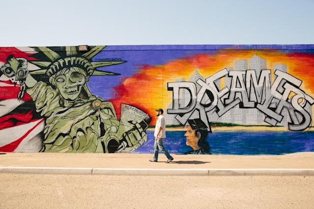 Recent graduate Edder Díaz Martinez walks past a mural near the Walter Cronkite School of Journalism and Mass Communication at Arizona State University on June 14 in Phoenix. (Photo: Caitlin O'Hara for Yahoo News)