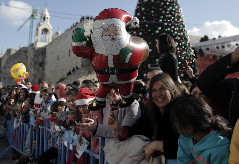 People gather to watch Christmas celebrations in Manger Square outside the Church of the Nativity as Christians gather for Christmas celebrations in the West Bank city of Bethlehem, on December 24, 2014 (AFP Photo/Ahmad Gharabli)