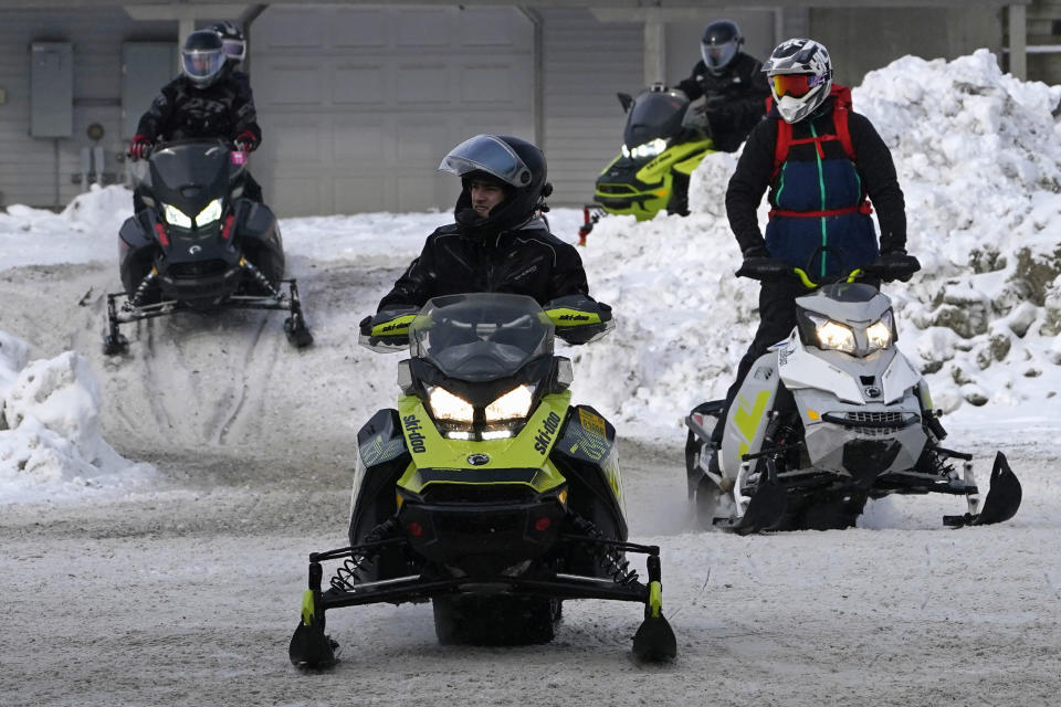 Snowmobile riders arrive in town, Saturday, Jan. 23, 2021, in Rangeley, Maine. The desire to get outside during the pandemic is creating the biggest boom in more than a decade for the snowmobiling industry. (AP Photo/Robert F. Bukaty)