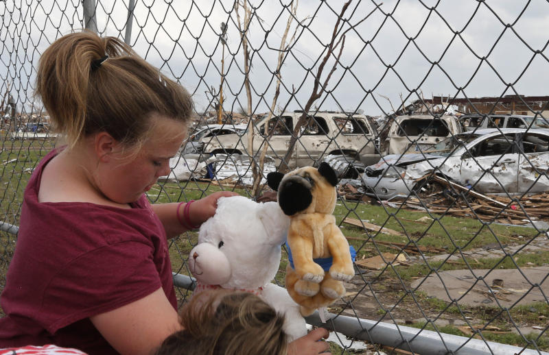 Ashlyn Kelley, age eleven, who is in the fifth grade and was in the Plaza Towers elementary school when the Moore tornado hit, ties stuffed animals to the perimeter fence as a memorial to the seven students who died, at the school in Moore, Okla., Friday, May 24, 2013. (AP Photo/Sue Ogrocki)