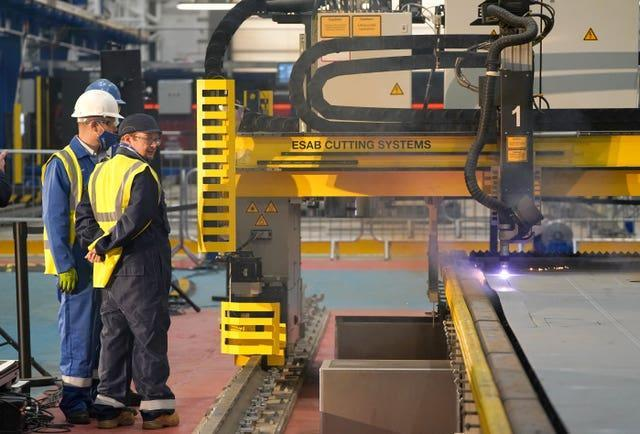 Workers watch a frigate steel cutting ceremony for the first of the class Type 31 frigate, at Babcock Rosyth, Fife