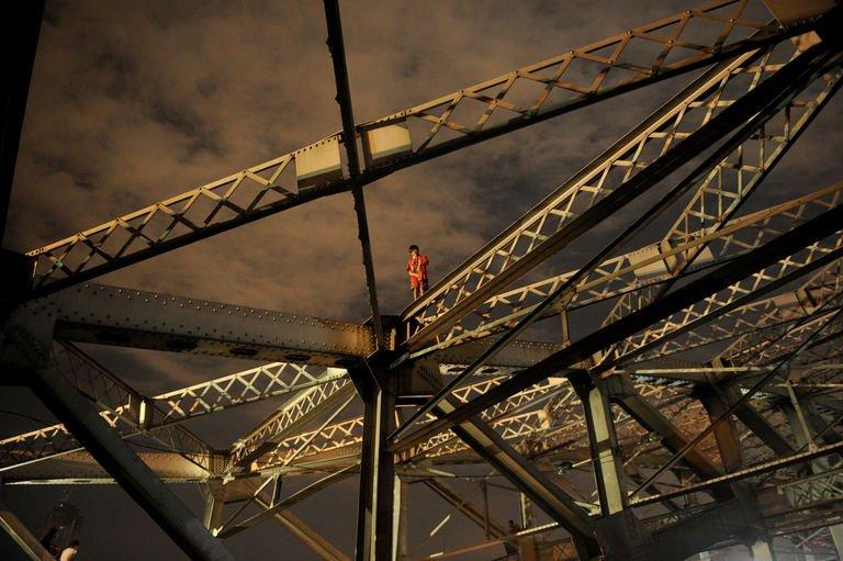 A homeless child stands on one of the trusses of the Quezon Bridge in Manila on January 27, 2013. The Philippines said Thursday its economy grew by a better-than-expected 6.6 percent last year as confidence rose in President Benigno Aquino's efforts to fight corruption and alleviate poverty