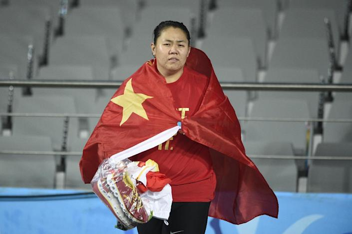 China's Zhang Wenxiu is wrapped in her national flag after winning the final of the Asian Games women's hammer in Incheon on September 28, 2014 (AFP Photo/Martin Bureau)