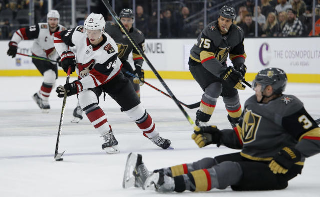 Arizona Coyotes center Carl Soderberg (34) skates around Vegas Golden Knights defenseman Brayden McNabb (3) during the first period of an NHL hockey game Friday, Nov. 29, 2019, in Las Vegas. (AP Photo/John Locher)