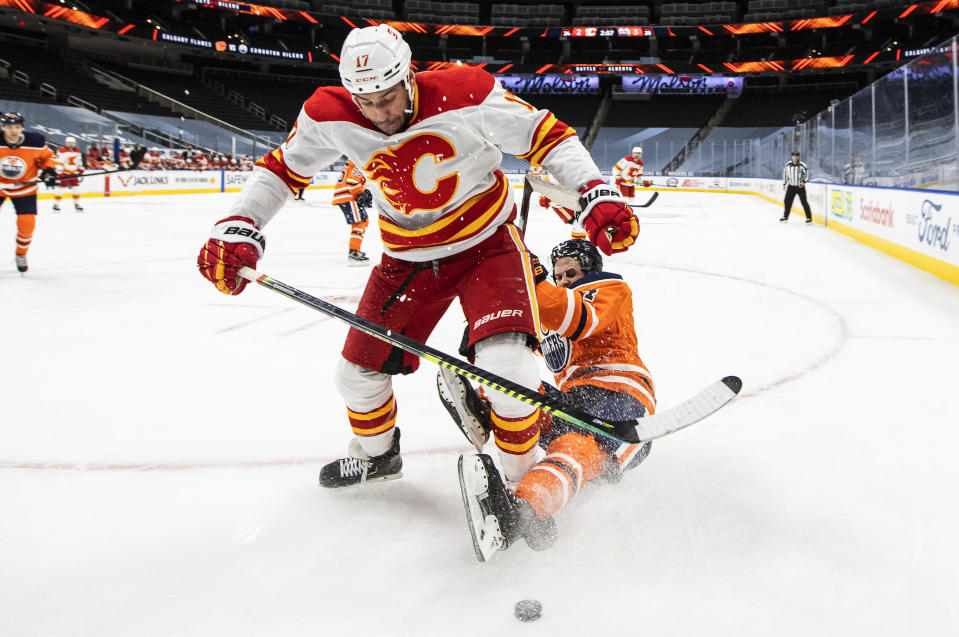 Edmonton Oilers' Kris Russell (4) is checked by Calgary Flames' Milan Lucic (17) during the third period of an NHL hockey game Friday, April 2, 2021, in Edmonton, Alberta. (Jason Franson/The Canadian Press via AP)