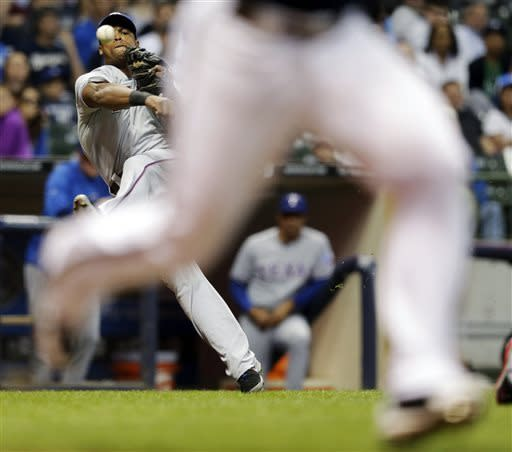 Texas Rangers third baseman Adrian Beltre makes a wild throw on a bunt by Milwaukee Brewers' Carlos Gomez during the fourth inning of a baseball game Wednesday, May 8, 2013, in Milwaukee. (AP Photo/Morry Gash)
