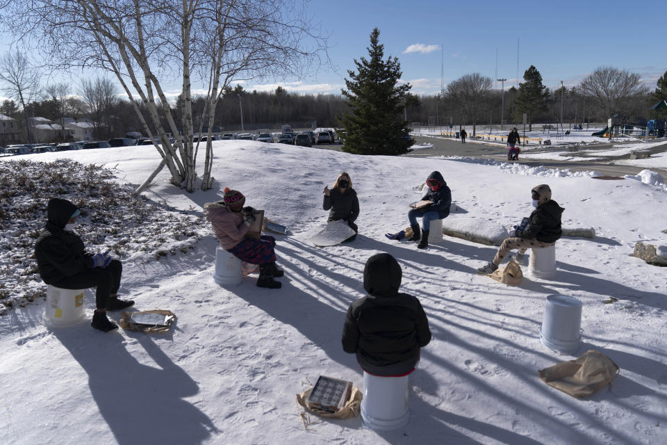 In this Monday, Dec. 8, 2020 photo, a fourth grade class uses upside-down buckets for seats as they study outside at the Gerald Talbot School, in Portland, Maine. The outdoors is considered to be the healthiest, safest place for kids to be during the pandemic. (AP Photo/Robert F. Bukaty)