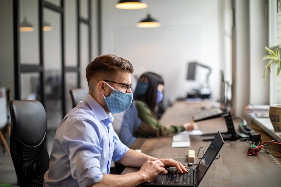 Businessman wearing protective face mask working at his desk. Business people back to work after pandemic sitting at desk with protection guard between them.