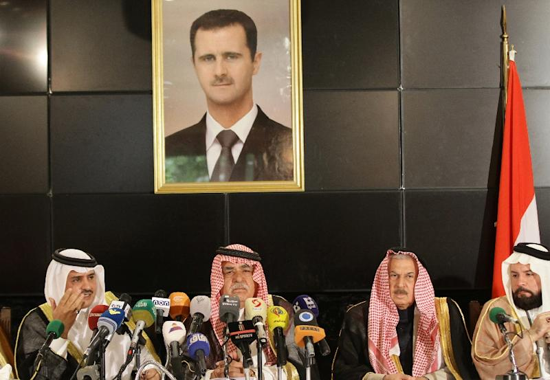 Sheikh Mohammed Faris (2nd from L), a member of the Tay tribe, sits under a portrait of Syrian President Bashar al-Assad as he chairs a press conference of Syria's leading pro-government tribes in Damascus on June 19, 2015