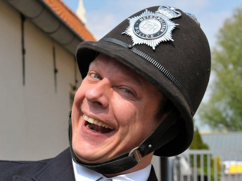 UK police officer laughing with helmet