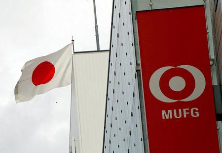 FILE PHOTO - Japan's national flag is seen behind the logo of  Mitsubishi UFJ Financial Group Inc (MUFG) at its bank branch in Tokyo, Japan September 5, 2017. REUTERS/Kim Kyung-Hoon