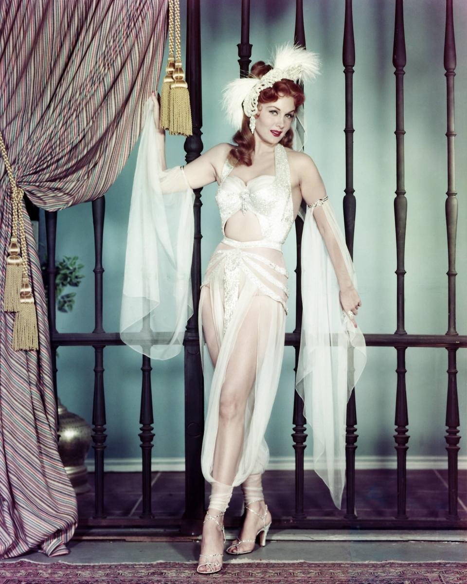 Rhonda Fleming, US actress, wearing a white sheer outfit, with white feathers in her hair, in a studio portrait, circa 1955.