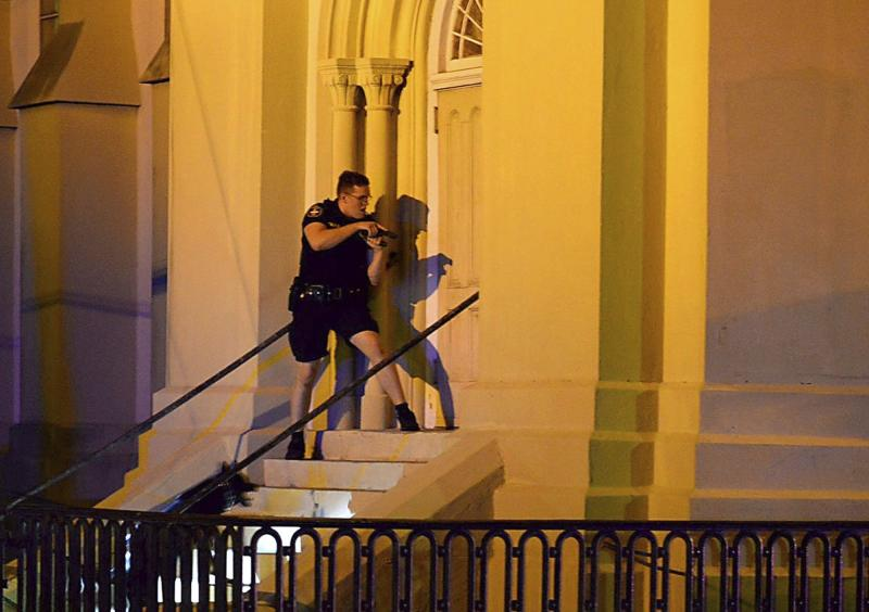 """FILE - In this June 17, 2015 file photo, a Charleston police officer searches for a shooting suspect outside the Emanuel AME Church, in downtown Charleston, S.C. he new documentary, """"Emanuel,"""" explores life after the tragic shooting took place on June 17, 2015, as family members, friends and the community try to heal through faith and forgiveness. (Matthew Fortner/The Post And Courier via AP, File)"""
