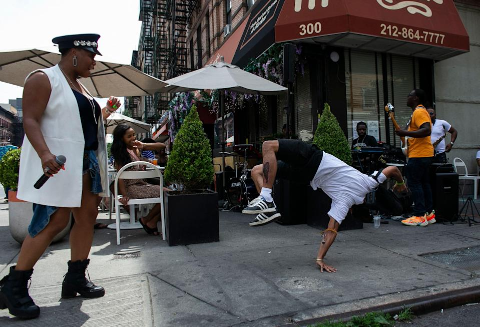 Performers dance, sing and play music outside a restaurant during the 28th annual Juneteenth celebration in the Harlem neighborhood of New York, on June 19, 2021.
