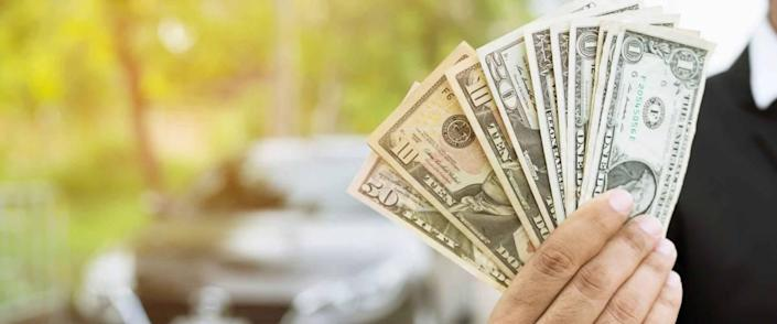Business man holding money in hand stand front car prepare pay by installments - insurance, loan and buying car concept