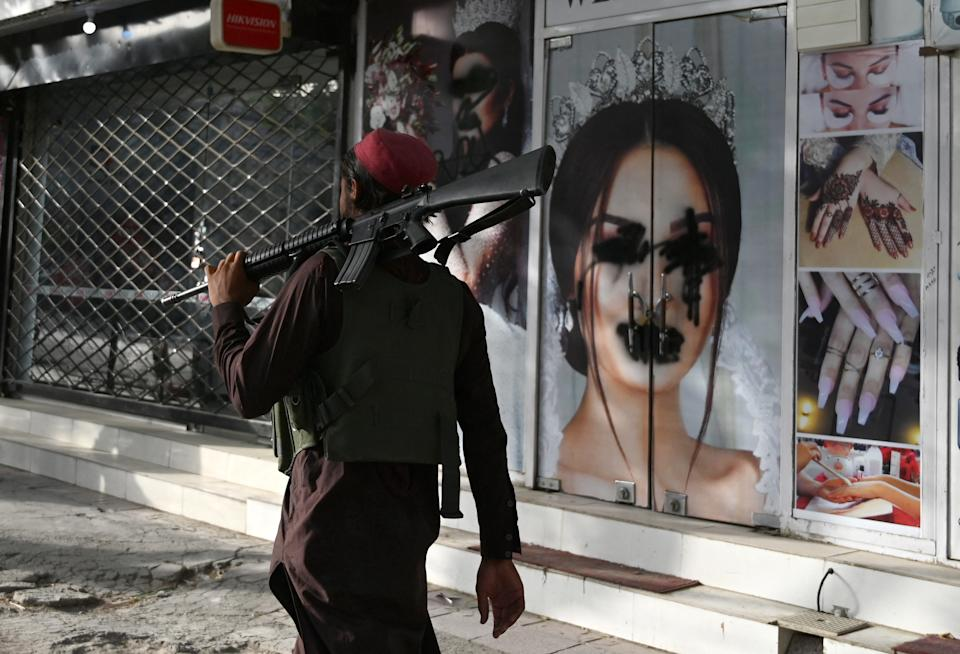 (FILES) In this file photo taken on August 18, 2021, a Taliban fighter walks past a beauty salon with images of women defaced using spray paint in Shar-e-Naw in Kabul.  US President Joe Biden said in an interview that aired August 19, 2021, that war is not the answer to growing fears for the human rights of women in Afghanistan after the Taliban takeover.