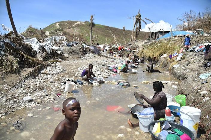 Haitians wash clothes in a river in Les Anglais, in Les Cayes, in the southwest of Haiti, on October 11, 2016 (AFP Photo/Hector Retamal)