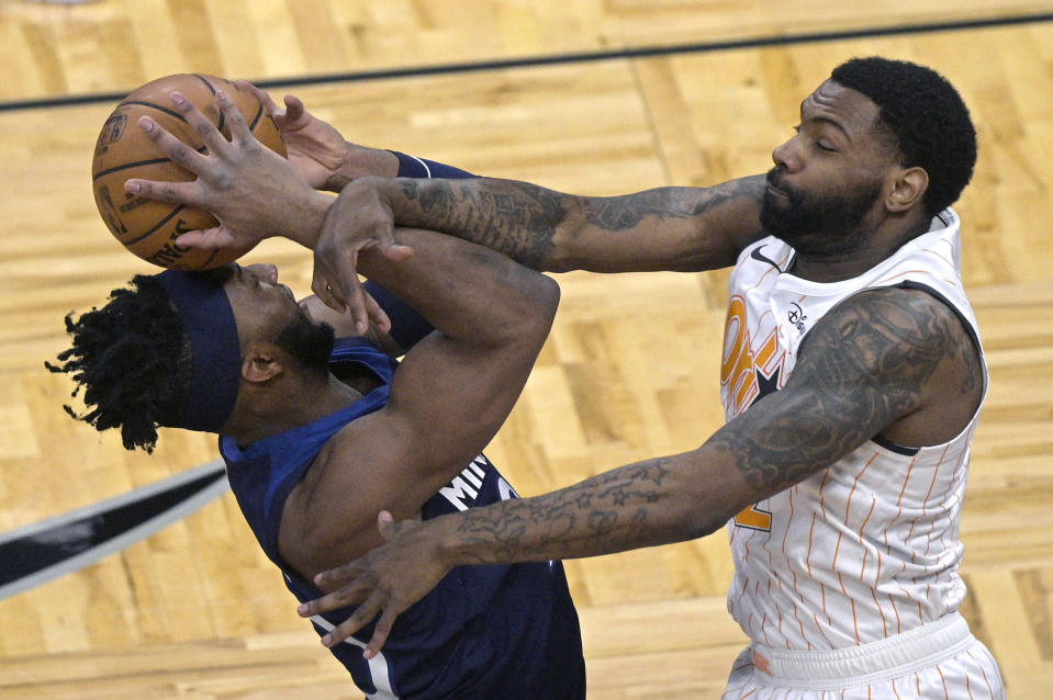 Minnesota Timberwolves forward Josh Okogie, left, is fouled by Orlando Magic guard Sindarius Thornwell while going up to shoot during the first half of an NBA basketball game, Sunday, May 9, 2021, in Orlando, Fla. (AP Photo/Phelan M. Ebenhack)