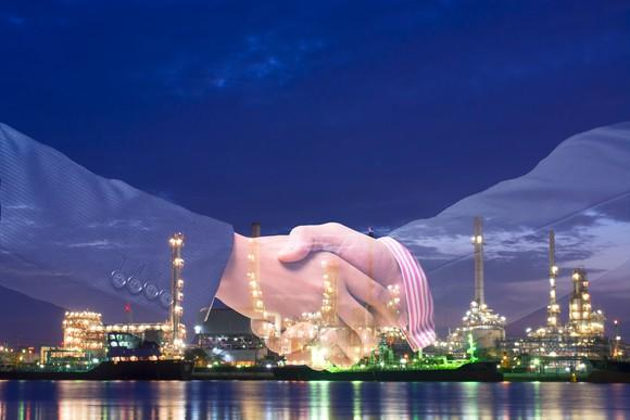 Double exposure of a handshake between two men, with a refinery at nighttime in the background.