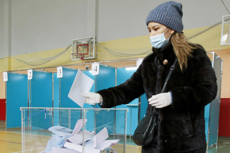 A woman wearing a face mask and gloves to protect herself against coronavirus, casts her ballot at a polling station during a parliamentary elections in Nur-Sultan, the capital city of Kazakhstan, Sunday, Jan. 10, 2021. (AP Photo)