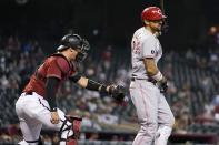 Arizona Diamondbacks catcher Carson Kelly, left, tags out Cincinnati Reds' Nick Castellanos, right, after a dropped third strike during the first inning of a baseball game Sunday, April 11, 2021, in Phoenix. (AP Photo/Ross D. Franklin)