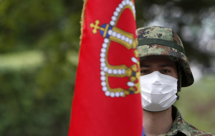 A Serbian army guard of honor with a national flag takes part in a welcoming ceremony for Serbian President Aleksandar Vucic during the vaccination at the army barracks in Belgrade, Serbia, Thursday, May 13, 2021. (AP Photo/Darko Vojinovic)