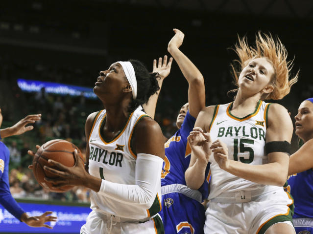 Baylor forward NaLyssa Smith, left, eyes the basket after pulling in a rebound from Morehead State while teammate Lauren Cox (15) looks on in the first half of an NCAA college basketball game, Monday, Dec. 30, 2019, in Waco, Texas. (Rod Aydelotte/Waco Tribune Herald, via AP)