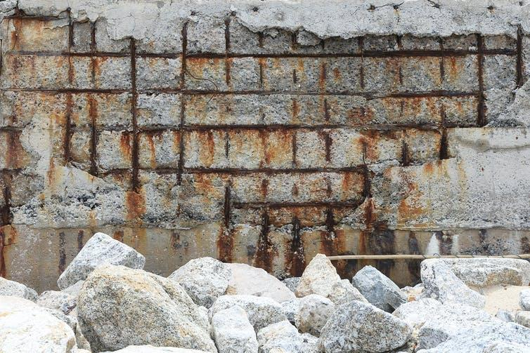 Crumbling reinforced concrete exposing rusted steel grid.