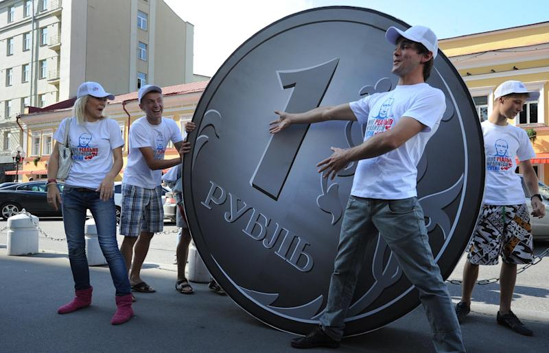 "Members of social network group ""I Really Like Putin"" perform in front of a two-meter Russian Ruble coin in Moscow on August 18, 2011"