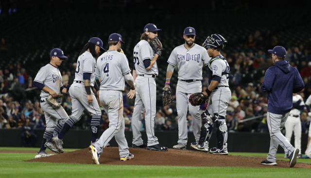 San Diego Padres relief pitcher Matt Strahm, center, stands on the mound and awaits a visit from Padres pitching coach Darren Balsley, right, during the seventh inning of a baseball game against the Seattle Mariners, Tuesday, Sept. 11, 2018, in Seattle. (AP Photo/Ted S. Warren)