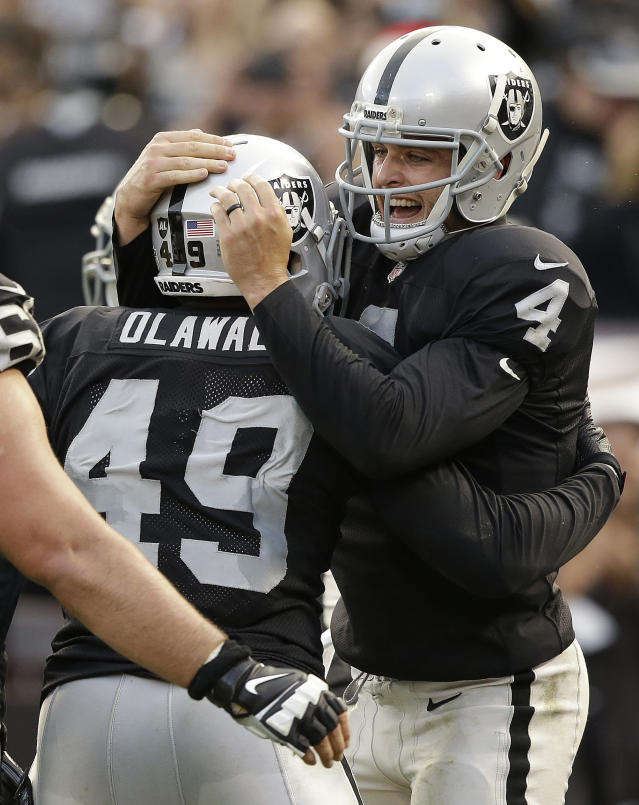 Oakland Raiders running back Jamize Olawale (49) and quarterback Derek Carr (4) celebrate after connecting on a 1-yard touchdown reception against the Buffalo Bills during the fourth quarter of an NFL football game in Oakland, Calif., Sunday, Dec. 21, 2014. (AP Photo/Marcio Jose Sanchez)