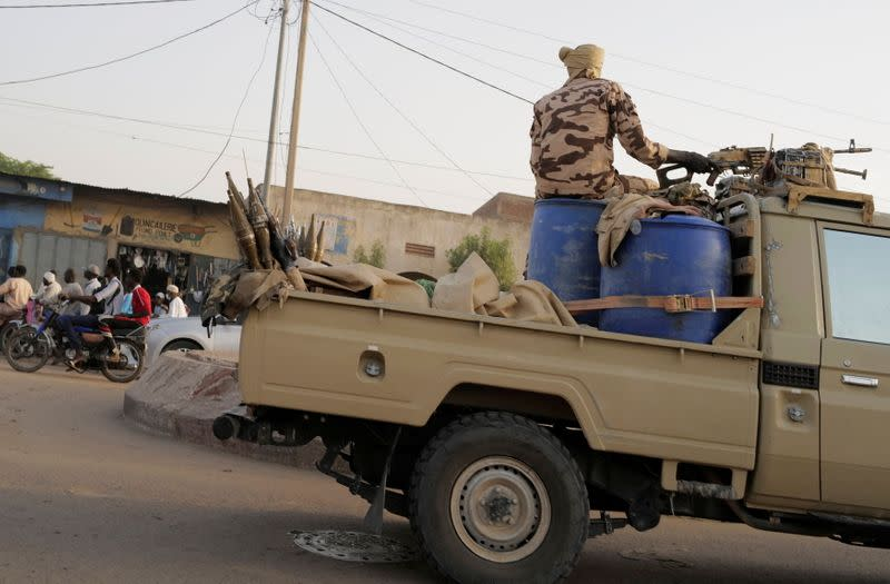 Members of the security forces drive along the market following the battlefield death of President Idriss Deby in N'Djamena