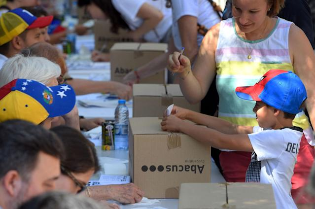 <p>A child casts a ballot during a symbolic plebiscite on Venezuelan president Maduro's project of a future constituent assembly, called by the Venezuelan opposition and held in Barcelona on July 16, 2017. (Lluis Gene /AFP/Getty Images) </p>