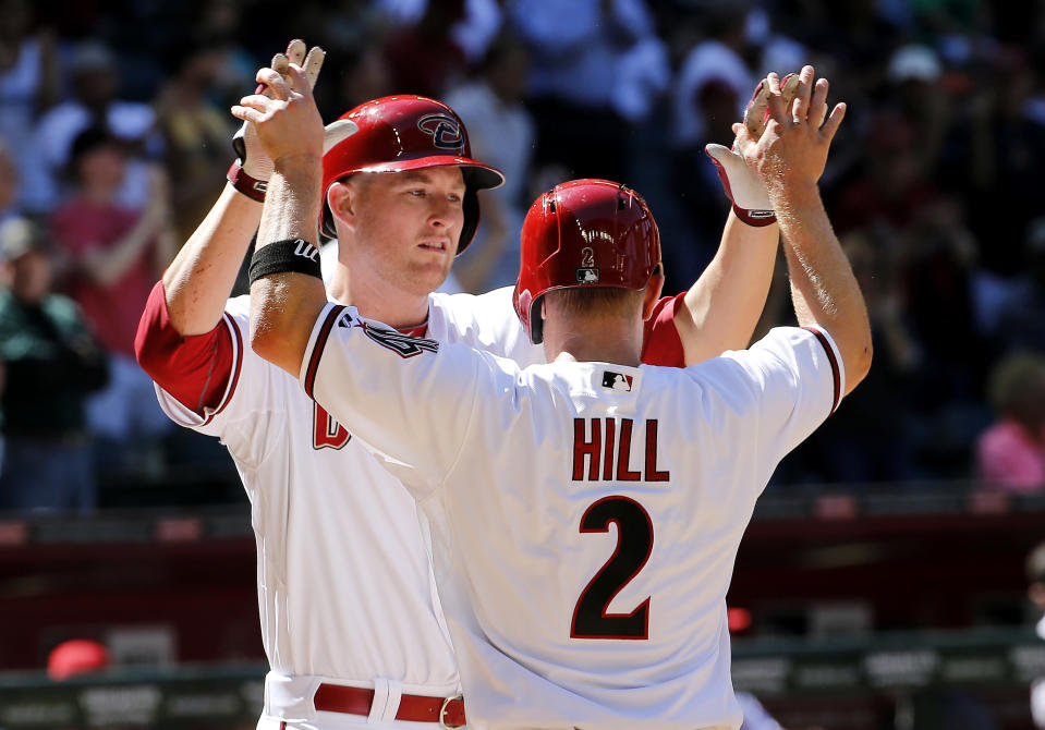 Arizona Diamondbacks' Mark Trumbo, left, high-fives teammate Aaron Hill (2) after hitting a two-run home run against the San Francisco Giants during the sixth inning of a baseball game on Thursday, April 3, 2014, in Phoenix. (AP Photo/Matt York)