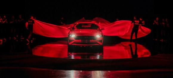 Ford pulling sheets off a Ford Mustang under red lighting at its China unveiling.