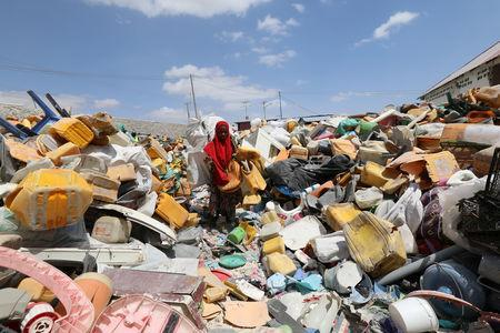 A woman sorts plastic litter collected from a garbage dump to be recycled into roofing tiles at the Envirogreen recycling plant in Mogadishu, Somalia January 13, 2019. Picture taken January 13, 2019. REUTERS/Feisal Omar