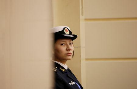 A female soldier of the People's Liberation Army (PLA) Navy stands guard at a news conference ahead of the 70th anniversary of the founding of Chinese People's Liberation Army Navy, in Qingdao, China, April 20, 2019. REUTERS/Jason Lee
