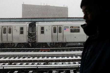 A commuter waits to catch the train during a late season snow storm in New York, U.S., March 21, 2018.  REUTERS/Lucas Jackson