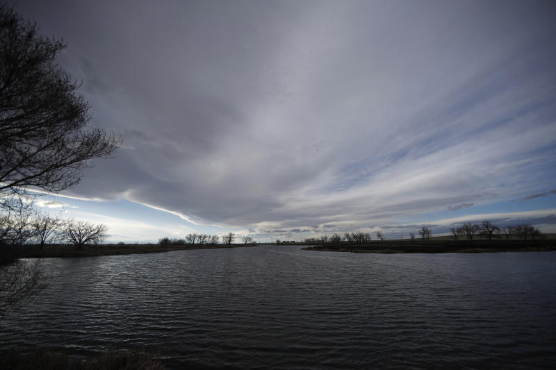 FILE - In this Sunday, April 14, 2019 file photo, clouds loom over a lake at the Rocky Mountain Arsenal National Wildlife Refuge Sunday, April 14, 2019, in Commerce City, Colo. Critics say Rocky Mountain Arsenal in Colorado illustrates the shortcomings of a cleanup designed to be good enough for a refuge but not for human habitation. (AP Photo/David Zalubowski)