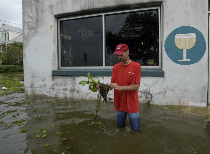 Cilton Bordelon picks up a plant washed into shore as he wades through storm surge from Lake Pontchartrain on Lakeshore Drive in Mandeville, La., as Hurricane Barry approaches on July 13, 2019. (Photo: Matthew Hinton/AP)