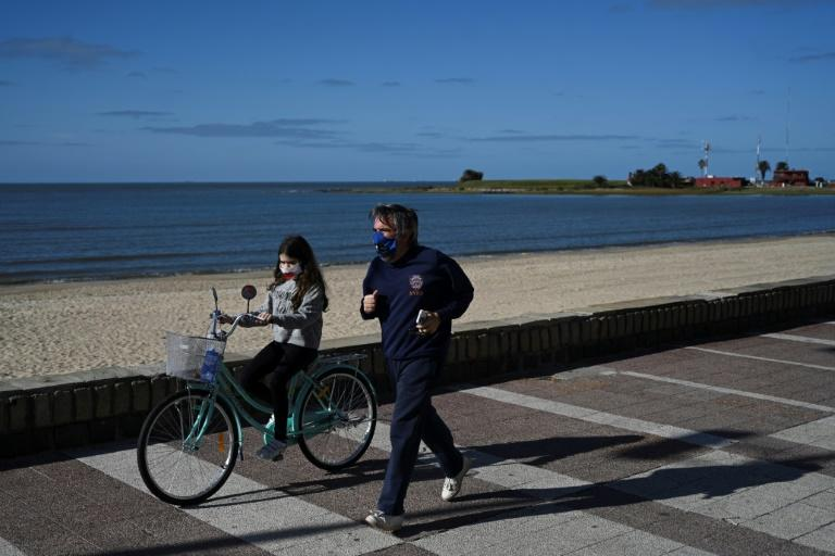 "A man and his daughter, both wearing masks, exercise on Montevideo's ""Rambla"" promenade (AFP Photo/Eitan ABRAMOVICH)"