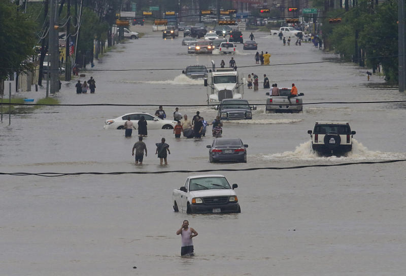 People walk through the flooded waters of Houston on Sunday. (THOMAS B. SHEA/Getty Images)